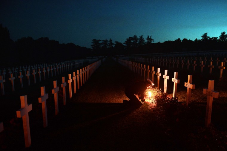 Torchlights are placed next to soldiers' tombs at the Douaumont's boneyard, eastern France, during the annual event known as The Four Days of Verdun, a night parade of veterans, as they commemorate the Verdun battle 98th anniversary. FREDERICK FLORIN/AFP/Getty Images