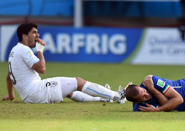 Uruguay's forward Luis Suarez (L) reacts past Italy's defender Giorgio Chiellini during a Group D football match between Italy and Uruguay at the Dunas Arena in Natal during the 2014 FIFA World Cup on June 24, 2014. JAVIER SORIANO/AFP/Getty Images