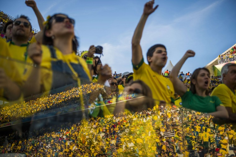 Brazilian football fans cheer as the opposite stand is reflected in a glass fence during a Group A football match between Brazil and Croatia at the Corinthians Arena in Sao Paulo during the 2014 FIFA World Cup on June 12, 2014. ODD ANDERSEN/AFP/Getty Images