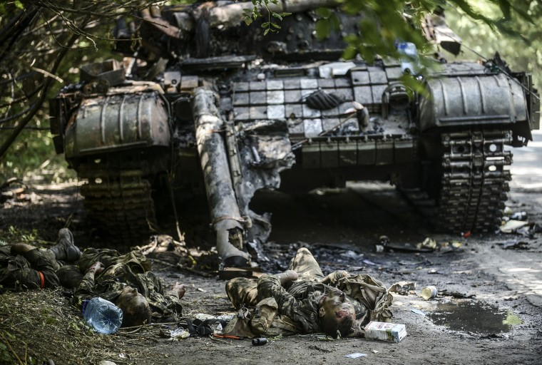 Bodies of crew members lie next to a destroyed Ukrainian tank in the northern outskirts of city of Donetsk, on July 22, 2014. Terrified civilians fled as intense clashes yesterday between Ukrainian government troops and pro-Russian rebels left at least four people dead on the outskirts of the insurgent bastion of Donetsk. A military spokesman said yesterday government troops were battling back control of the districts around the airport and had broken through the rebel cordon to reach their comrades inside. BULENT KILIC/AFP/Getty Images