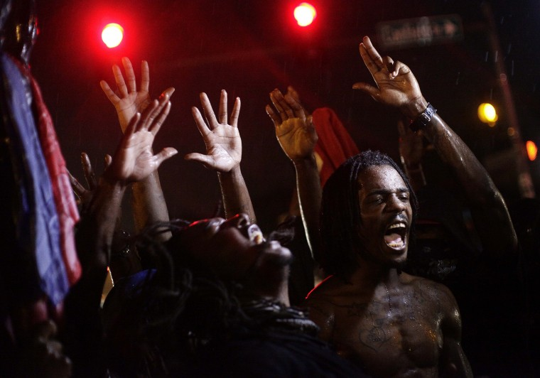 Demonstrators protest against the August 9 police shooting of 18-year-old Michael Brown by holding their hands up while gathered on the streets of Ferguson, Missouri late on August 16, 2014. A crowd of some 200 demonstrators defied a curfew that came into effect in Ferguson early on August 17, days after police shot dead the unarmed black teen, triggering a wave of rioting. JOSHUA LOTT/AFP/Getty Images
