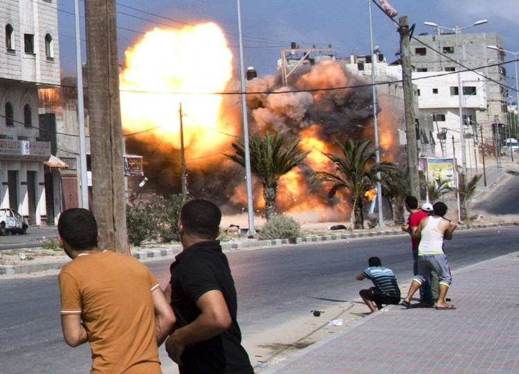 Palestinian men look on as a bomb from an Israeli air strike hits a house in Gaza City on August 23, 2014. Israel kept up the pressure on Hamas in Gaza, carrying out multiple air strikes that killed six Palestinians, five of them from the same family, as Egypt prepared to convene new truce talks. ROBERTO SCHMIDT/AFP/Getty Images