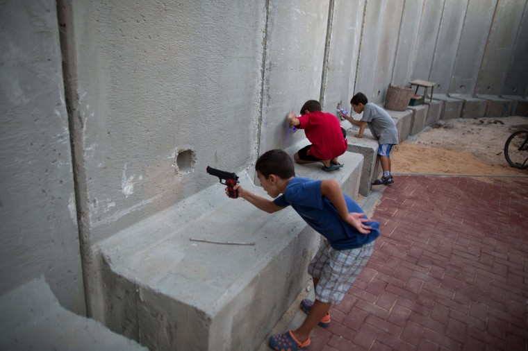 Israeli children hold toy guns as they pretend to play war games next to newly built protection cement walls around a kindergarten in the center of Kibbutz Nahal Oz located near the border with Gaza Strip on September 8, 2014. Since the ceasefire between Israel and Hamas militants, following fifty days of fighting, most Israeli residents living near the border with the Palestinian enclave returned to their homes with the army on high alert and new security measures to protect them. MENAHEM KAHANA/AFP/Getty Images