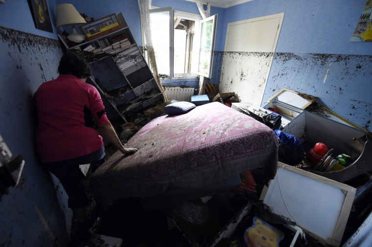A woman looks at the damages in her house after a flood, on September 18, 2014, in Lamalou-les-Bains, southern France. Five people died when storms turned a peaceful river that bordered their camping site in southern France into a raging torrent that swept them away, rescue workers said on September 18. The site in Lamalou-les-Bains was devastated by the flood overnight as storms that had already killed an elderly lady in the nearby region of Aveyron also left a person missing in another neighbouring department. PASCAL GUYOT/AFP/Getty Images