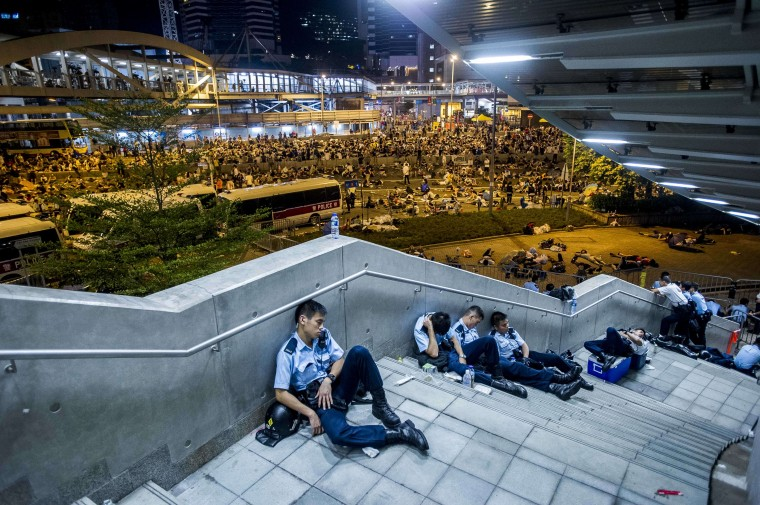 Policemen rest following pro-democracy protests in Hong Kong on September 29, 2014. Police fired tear gas as tens of thousands of pro-democracy demonstrators brought parts of central Hong Kong to a standstill in a dramatic escalation of protests that have gripped the semi-autonomous Chinese city for days. XAUME OLLEROS/AFP/Getty Images
