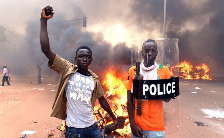 Protesters pose with a police shield outside the parliament in Ouagadougou on October 30, 2014 as cars and documents burn outside. Hundreds of angry demonstrators in Burkina Faso stormed parliament on October 30 before setting it on fire in protest at plans to change the constitution to allow President Blaise Compaore to extend his 27-year rule. Police had fired tear gas on protesters to try to prevent them from moving in on the National Assembly building ahead of a vote on the controversial legislation. But about 1,500 people managed to break through the security cordon and were ransacking parliament. ISSOUF SANOGO/AFP/Getty Images