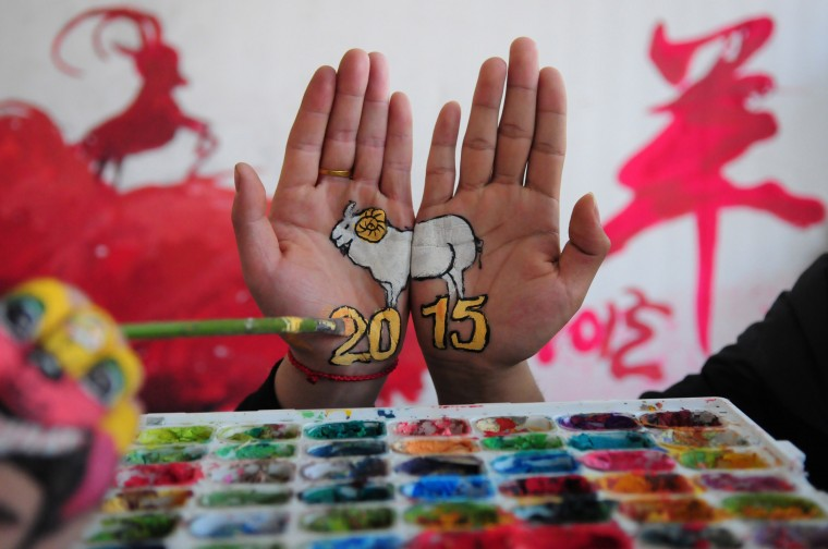 """This photo taken on December 30, 2014 shows a college student with paintings of a sheep on their hands to welcome the new year, and to mark the coming """"Year of the Sheep"""", in Liaocheng, in eastern China's Shandong province. The Year of the Sheep, according to the lunar new year calendar, will start on February 19, 2015. (AFP/Getty Images)"""