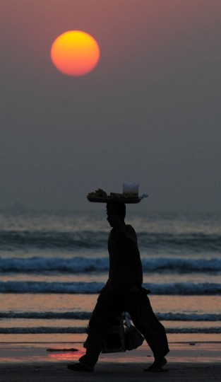 A Pakistani vendor walks at Clifton beach during the last sunset of the year in Karachi on December 31, 2014. (Asif Hassan/AFP/Getty Images)