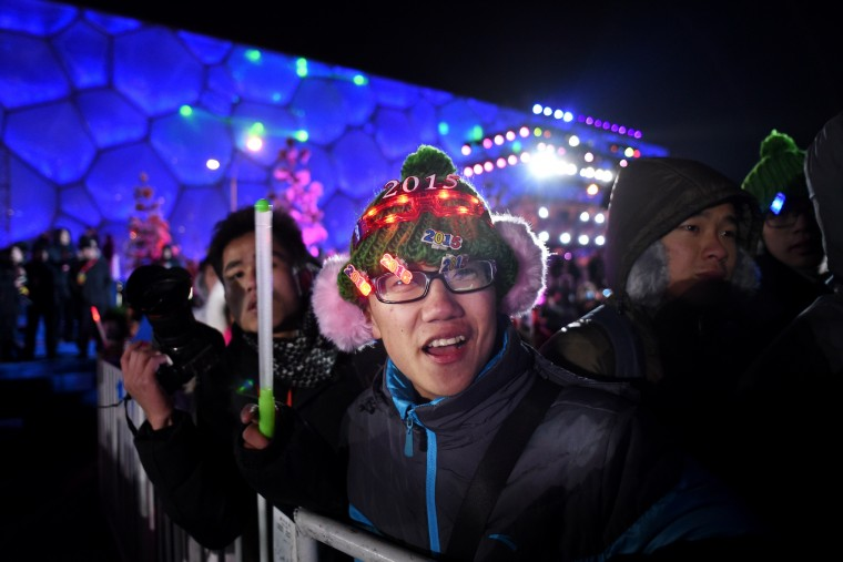 A man (C) cheers during the New Year's Eve countdown event in front of Beijing's National Stadium, Known as the Bird's Nest in Beijing on December 31,2014. Beijing is bidding to host the 2022 Winter Olympic Games, with a decision on the winning city to be made in July 2015. (Wang Zhao/AFP/Getty Images)