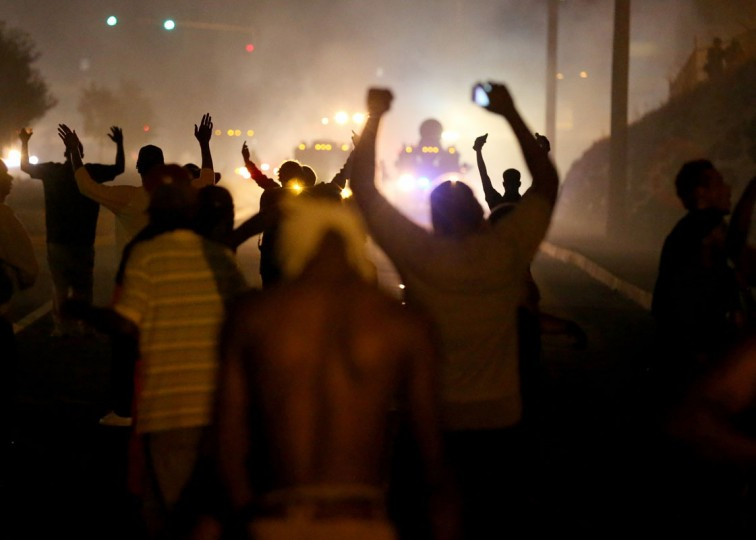 Hundreds of protesters protested throughout the later part of the year in a St. Louis suburb where Michael Brown, 18, was shot to death by a police officer on Aug. 9. Here, demonstrators hold up their hands as police fire tear gas at them as they protest the shooting death of Michael Brown on August 17, 2014 in Ferguson, Missouri. Police sprayed pepper spray, shot smoke, gas and flash grenades as violent outbreaks have taken place in Ferguson since the shooting death of Michael Brown by a Ferguson police officer on August 9th. (Photo by Joe Raedle/Getty Images)