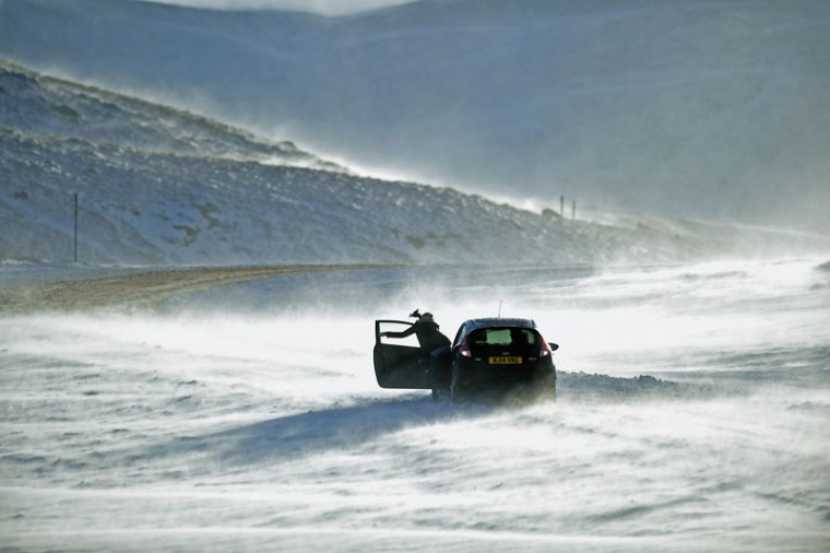People push a car stuck on the A93 Braemar to Glenshee road as snow is forecast for much of the UK on December 8, 2014 in Glenshee, Scotland. The Met Office yellow 'Be Aware' warning remains in place across the country, with drivers struggling with snow fall overnight. (Jeff J Mitchell/Getty Images)