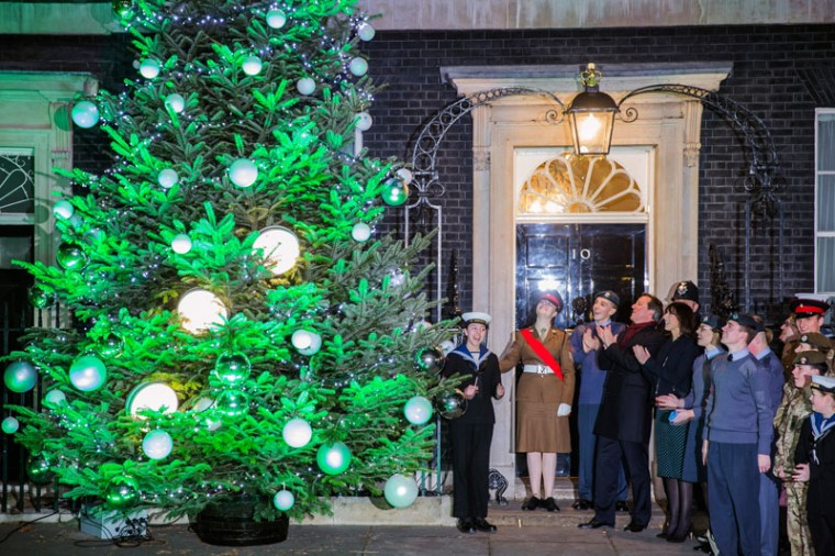 British Prime Minister David Cameron and wife Samantha Cameron join military and their families at the lighting of Downing Street's Christmas tree at 10 Downing Street on December 8, 2014 in London, England. Oxfordshire tree Colin Griffith, from Dinmore Hill Trees at Festive Farm in Wellington, Hereford was selected to supply a pine tree to grace the steps of the prime ministers official residence in 2014. (Dan Kitwood/Getty Images)