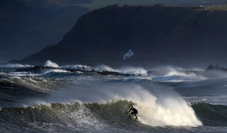 Professional surfer Alastair Mennie braves the conditions as he catches a wave in Ballycastle, Northern Ireland. High winds and large waves hit the North West Coast of the UK and Northern Ireland today. In the background sits Guglielmo Marconi's cottage which was home to the Italian inventor credited as the inventor of radio, (Charles McQuillan/Getty Images)