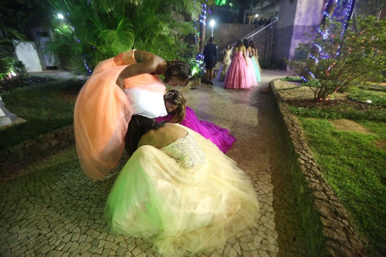 Debutantes help another prepare while waiting to enter their debutante ball in Rio de Janeiro, Brazil. The gala was held in a posh tennis club and organized by the Pacifying Police Unit (UPP) from the Babilonia and Chapeu Mangueira communities, or favelas. Volunteers prepared makeup, hair styling and loaned dresses in an effort to build goodwill between favela residents and the community's police force. Eleven girls from the favelas, aged around 15-years-old, attended the ball along with police officers, family members and supporters. (Mario Tama/Getty Images)