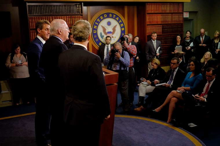 Sen. Patrick Leahy (D-VT), center, with Sen. Jeff Flake (R-AZ), left, and Rep. Chris Van Hollen (D-MD), talk about their efforts to retrieve U.S. contractor Alan Gross from prison in Cuba on December 17, 2014 in Washington, DC. The three lawmakers flew to Cuba to bring Gross, held in Cuba since 2009, back to the United States. U.S. President Barack Obama announced today plans to restore diplomatic relations with Cuba, over 50 years after they were severed in January 1961. (Photo by T.J. Kirkpatrick/Getty Images)
