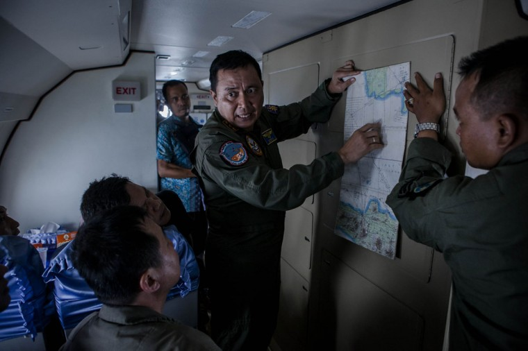 A member of the Indonesian military reads a map during a search and rescue (SAR) mission over the waters of the Java Sea near Pangkalan Bun, Kalimantan on December 30, 2014 in Surabaya, Indonesia. Debris and dead bodies have reportedly been sighted in the Java Sea during search operations for the missing AirAsia flight QZ 8501. AirAsia flight QZ8501 from Surabaya to Singapore, with 162 people on board, lost contact with air traffic control at 07:24 a.m. local time on December 28. (Ulet Ifansasti/Getty Images)