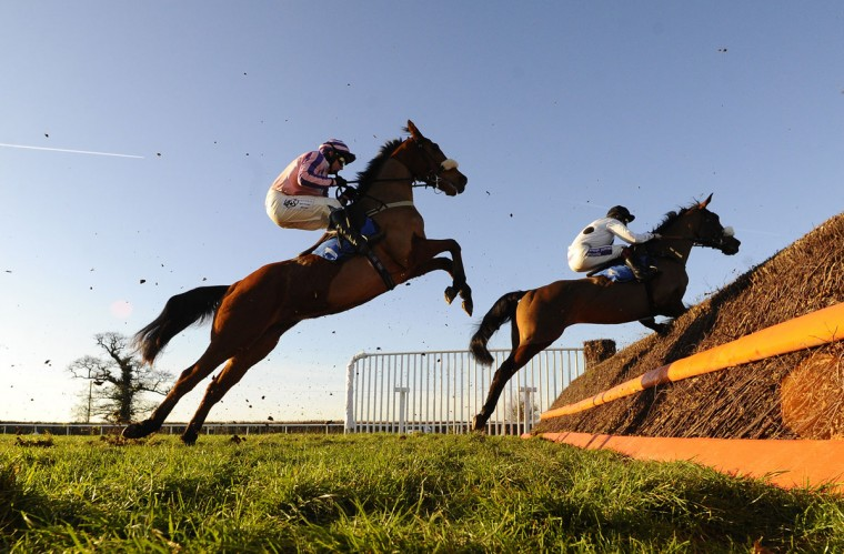 Paul Moloney riding Allez Vic (L) stand well of the fence whilst jumping at Taunton racecourse on December 30, 2014 in Taunton, England. (Alan Crowhurst/Getty Images)