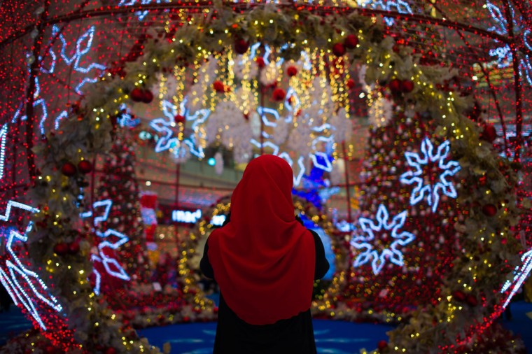 A woman takes pictures of Christmas decorations at a shopping mall in Kuala Lumpur on November 29, 2014. As Christmas approaches, Malaysia's shopping malls are decorated with lights and advertising displays to lure shoppers. (Mohd Rafsan/AFP/Getty Images)