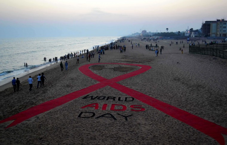 Indian residents walk past a sand sculpture incorporating what is aimed to be the worlds longest red ribbon created by sand artist Sudarsan Pattnaik at Puri beach, some 65 kms from Bhubaneswar on November 30, 2014. World AIDS Day is marked annually on December 1. (Asit Kumar/AFP/Getty Images)