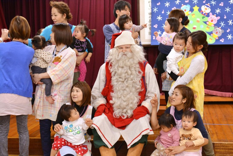 A man dressed as Santa Claus (C) from Finland poses with children as part of his visit to the Hinomoto nursery school in Tokyo on December 1, 2014. The Santa is here as a goodwill ambassador of Finnair until December 24. (Kazuhiro Nogi/AFP/Getty Images)