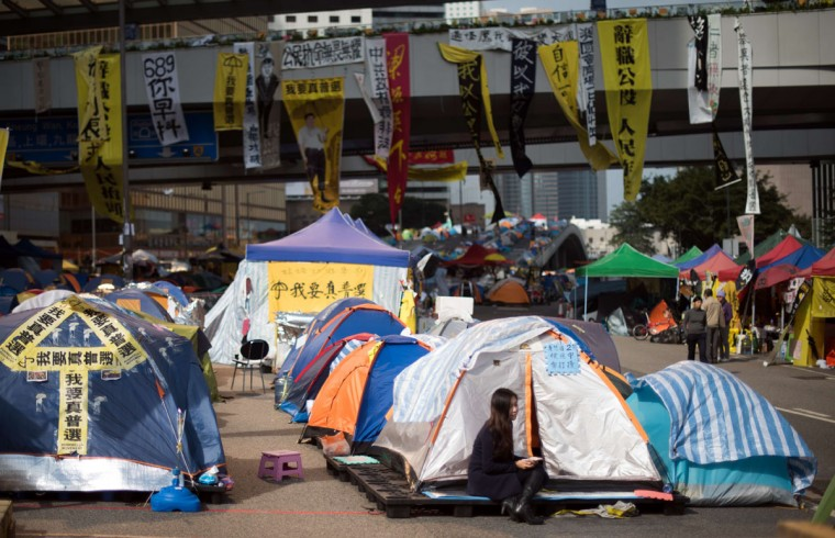 """A girl sits outside a tent at the movement's main protest site in the Admiralty district of Hong Kong on December 6, 2014. Benny Tai, a founder of Hong Kong's pro-democracy Occupy movement branded the occupation of the city's main roads as """"high-risk"""" , urging protesters to turn to new methods of civil disobedience to push for electoral reform. (JOHANNES EISELE/AFP/Getty Images)"""