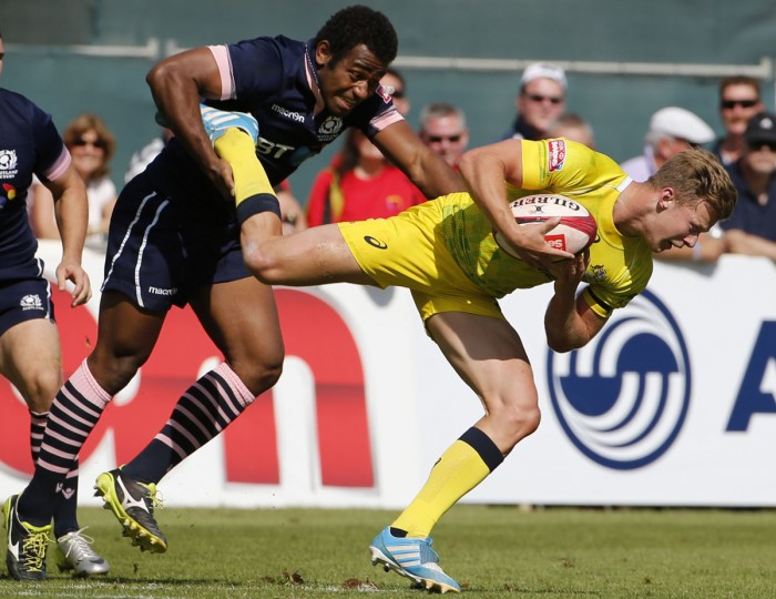 Joe Nayacavou (center) of Scotland tackles Cameron Clark (right) of Australia during their quarter-final rugby match in the Dubai leg of IRB's Sevens World Series on December 6, 2014. (KARIM SAHIB/AFP/Getty Images)