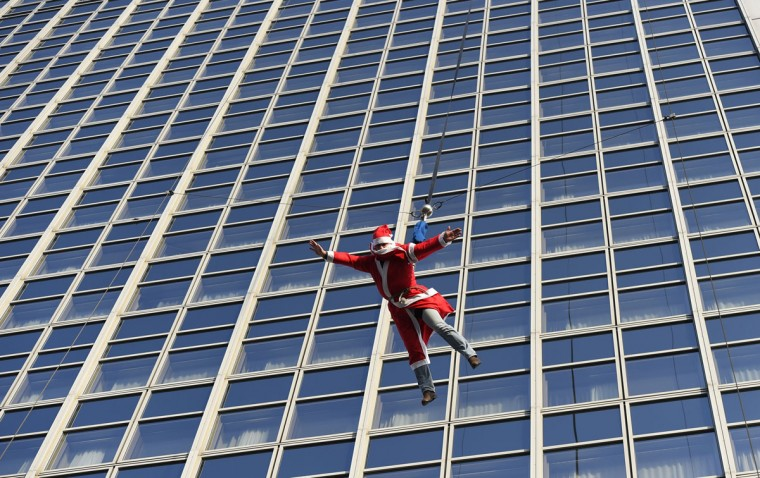 A man dressed as Father Christmas makes a base flying jump from the top of the Forum hotel in Berlin's district December 6, 2014. (TOBIAS SCHWARZ/AFP/Getty Images)