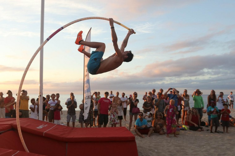"""French Olympic pole vault champion and world record holder Renaud Lavillenie participates in a demonstration during """"Boucan Perche"""" on the beach of Boucan Canot, on the west coast of the French Indian Ocean island of La Reunion on December 6, 2014. (RICHARD BOUHET/AFP/Getty Images)"""