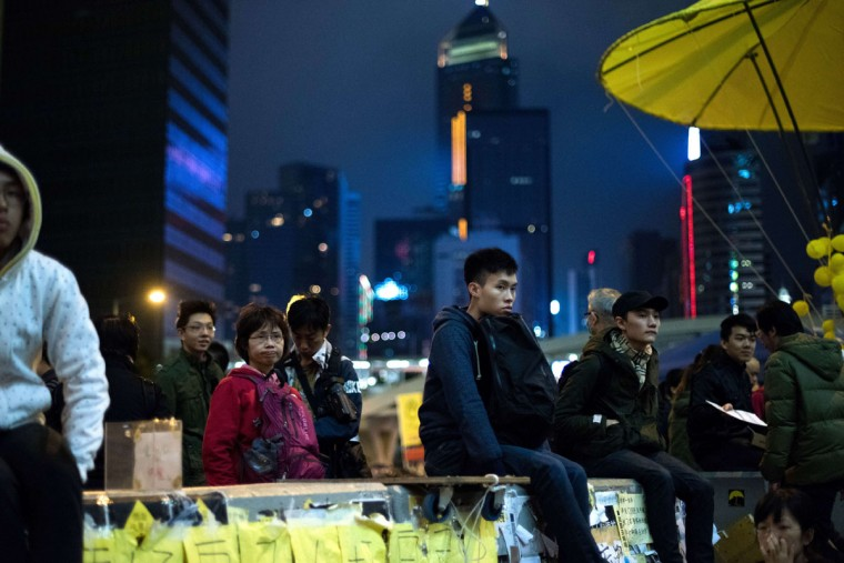 People sit on a wall as they listen to a speaker at the movement's main protest site in the Admiralty district of Hong Kong on December 6, 2014. Joshua Wong, the teenage face of Hong Kong's pro-democracy movement, said he has ended a four-day hunger strike designed to force the government into further talks on political reform. (JOHANNES EISELE/AFP/Getty)