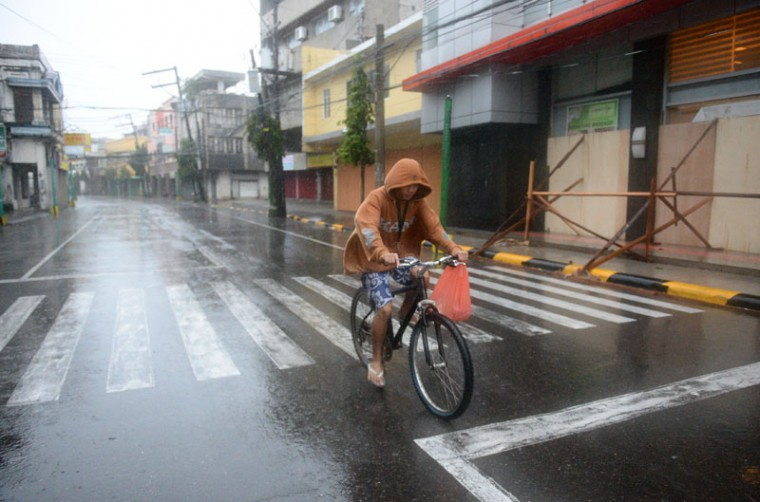 A resident cycles around an empty street hours before Typhoon Hagupit passes near the city of Legazpi on December 7, 2014. Typhoon Hagupit tore apart homes and sent waves crashing through coastal communities across the eastern Philippines, creating more misery for millions following a barrage of deadly disasters. (Ted Aljibe/AFP/Getty Images)