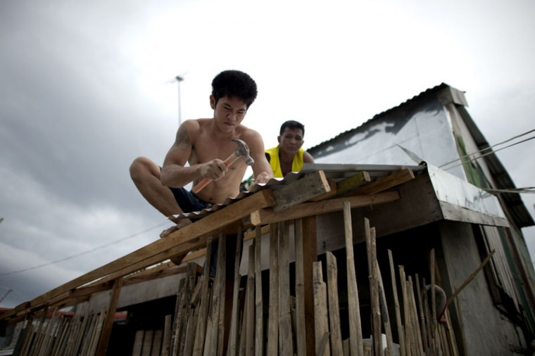 Workers reinforce the roof of a house at the port area in Manila on December 7, 2014 ahead of the arrival of Typhoon Hagupit. Shanties at the bay of Manila will be affected as Typhoon Hagupit will pass near Manila. Typhoon Hagupit tore apart homes and sent waves crashing through coastal communities across the eastern Philippines on December 7, creating more misery for millions following a barrage of deadly disasters. (Noel Celis/AFP/Getty Images)