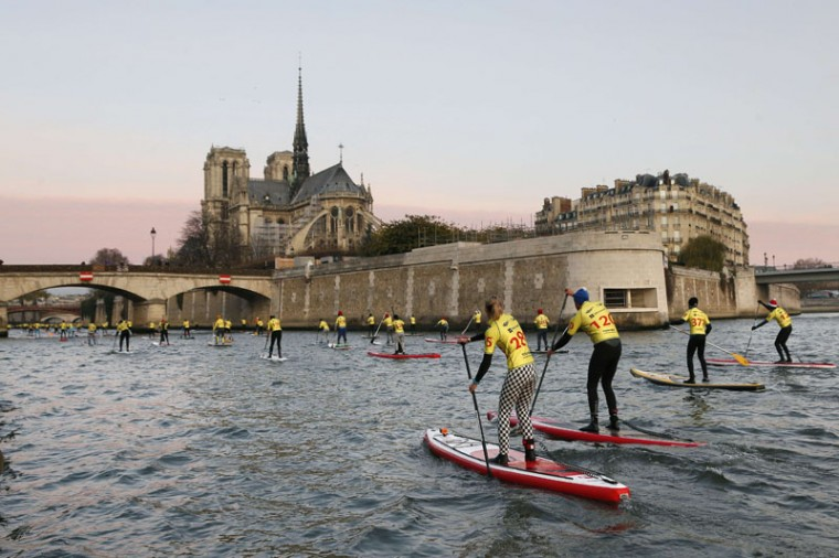 Participants ride stand up paddles (SUP) on the Seine river in Paris. (Thomas Samson/AFP/Getty Images)
