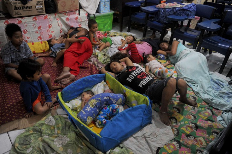 Evacuees are seen at the Government Elementary School turn into an evacuation center in Manila on December 8, 2014. Greenpeace global chief Kumi Naidoo said increasingly violent storms hitting the Philippines showed the world had to act on climate change, as Typhoon Hagupit barrelled across the country. (Jay Directo/AFP/Getty Images)