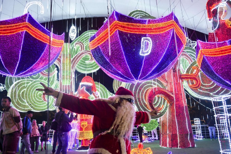 A man dressed as Santa Claus gestures next to the Christmas lights on December 9, 2014 in Medellin, Antioquia department, Colombia. (Raul Arboleda/AFP/Getty Images)