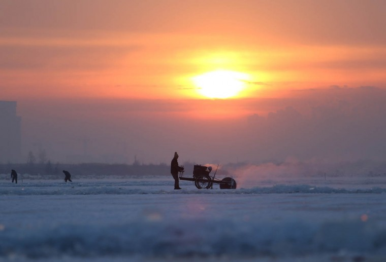 People cut ice blocks that are used for Harbin international ice and snow festival from the frozen Songhua river in Harbin, northeast China's Heilongjiang province. As China's most famous and popular winter attraction, the annual festival is set to kick off on January 5, 2015 and last for a month, local media reported. (Getty Images)
