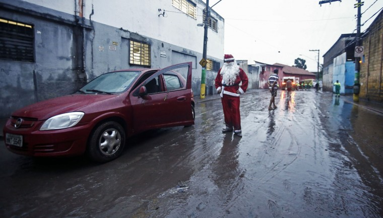A man disguised as Santa Claus stands on a street after heavy rains at Itaquera neighborhood in Sao Paulo, Brazil on December 10, 2014. (Miguel Schincariol/AFP/Getty Images)