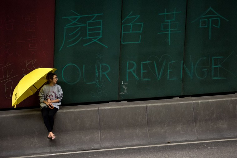 "A woman holds a yellow umbrella -- a symbol of the pro-democracy protests in Hong Kong -- next to graffiti that reads ""Our Revenge"" inside a blockaded tunnel on a highway in the Central district of Hong Kong, hours before police were expected to move in to clear pro-democracy protesters on December 11, 2014. Hong Kong authorities are preparing for the final clearance of the city's main pro-democracy protest site after more than two months, reports said, with an injunction paving the way for bailiffs to swoop. (Alex Ogle/AFP/Getty Images)"