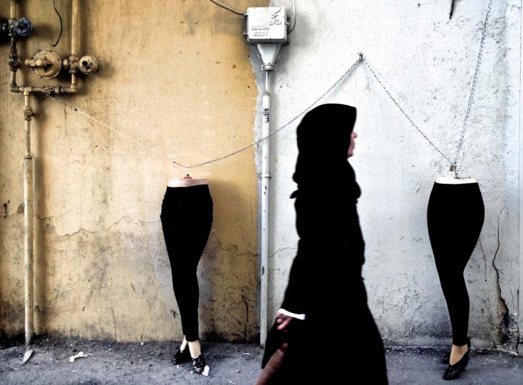 An Iranian woman walks past mannequins locked to a gas pipe in northern Tehran on December 15, 2014. (Behrouz Mehiri/AFP/Getty Images)