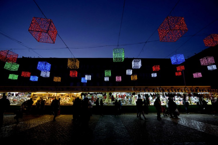 People look at the stands at the Christmas market set up under lights illuminating Plaza Mayor in the centre of Madrid on December 11, 2014. (Dani Pozo/AFP/Getty Images)