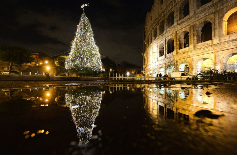 A picture taken at night shows lights on a Christmas tree and the Colosseum on December 16, 2014 in Rome. (Tiziana Fabi/AFP/Getty Images)