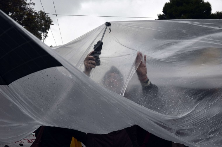 Laid off public sector workers protect themselves from heavy rain as they march in central Athens on December 17, 2014 . Lawmakers from December 17, 2014 will vote for a new Greek president in a ballot that will lead to snap general elections if they fail -- putting on the line years of efforts to turn around an economy in crisis. Louisa Gouliamaki/AFP/Getty Images