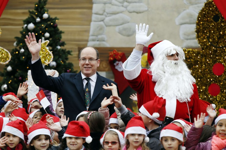 Prince Albert II of Monaco waves next to a man wearing a Santa Claus costume during the Children's Christmas ceremony on December 17, 2014 at the Monaco Palace. (Valery Hache/AFP/Getty Images)