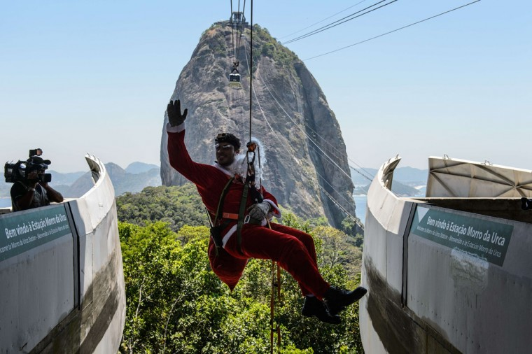 A man disguised as Santa Claus waves to people after getting his fake beard stuck on the pulley after sliding down, at Sugar Loaf Mountain in Rio de Janeiro, Brazil, on December 18, 2014. (Yasu Yoshi Chiba/AFP/Getty Images)