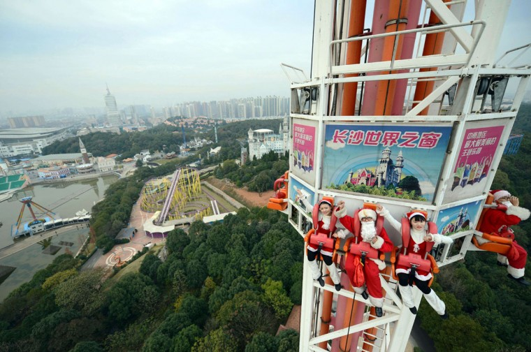 This picture taken on December 18, 2014 shows employees wearing Christmas costumes on a free-fall ride at a theme park in Changsha, central China's Hunan province. The park organized a series of Santa Claus-themed events ahead of Christmas. (AFP/Getty Images)