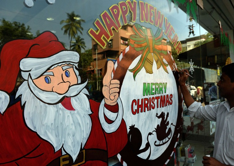 An Indian artist gives finishing touches to a Christmas-themed glass painting on the window of a showroom of electronics giant Sony in Mumbai on December 18, 2014. Even though Christians account for just over 2 percent of the billion plus strong Indian population Christmas is celebrated with great fervor in the country. Shopkeepers and entrepreneurs decorate their outlets in festive themes and offer special discounts to woo customers. (Indranil Mukherjee/AFP/Getty Images)