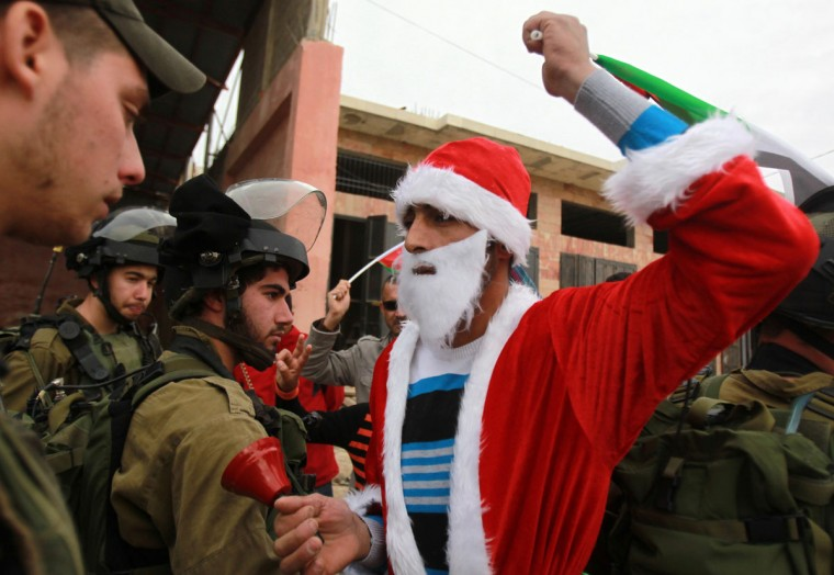 A Palestinian man, wearing a Santa Claus costume and waving the national flag, is confronted by Israeli soldiers during a weekly demonstration on December 19, 2014 against Israel's controversial separation barrier, in the village of Maasarah, near the biblical West Bank city of Bethlehem. (Musa Al-Shaer/AFP/Getty Images)