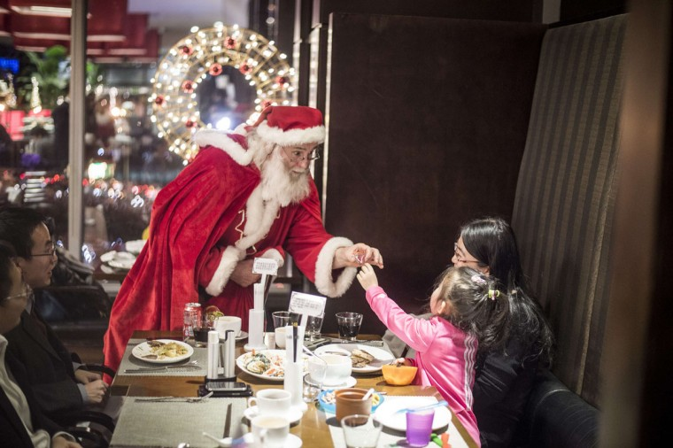 A Santa Claus salutes a girl at the Intercontinental hotel of Beijing, on December,19, 2014. (Fred Dufour/AFP/Getty Images)
