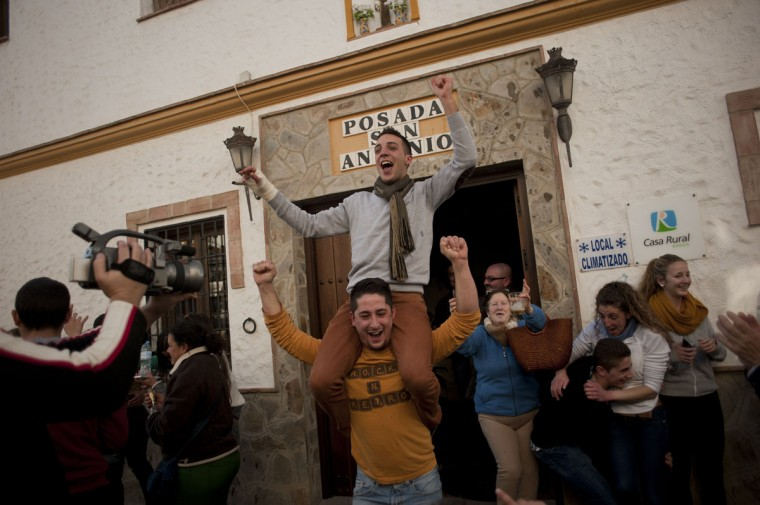 "Spanish Christmas lottery winners celebrate in El Bosque, Cadiz province, after having won the first prize in Spain's Christmas lottery named ""El Gordo"" (Fat One) on December 22, 2014. This year's winning number is 13437 representing takings of 4 million euros. (Jorge Guerrero/AFP/Getty Images)"