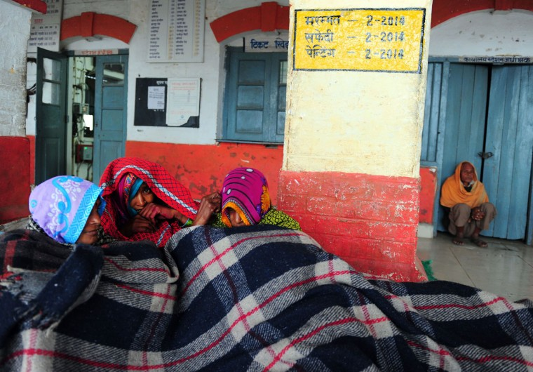 Indian passengers gather under a blanket as they wait for a train at Daraganj railway station in Allahabad on December 22, 2014. Dense winter fog has enveloped the Indian capital and much of northern India with the low visibility affecting road, rail and air traffic. (Sanjay Kanojia/AFP/Getty Images)