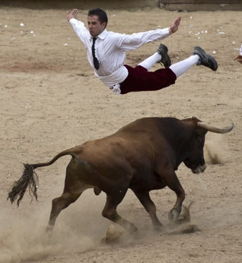 "A man jumps over a bull during a ""recortadores"" bullfight at the Canaveralejo bullring in Cali, Department of Valle del Cauca, Colombia, on December 21, 2014. The recortadores bullfight is an ancient tradition in which men try to dodge the bull without a cape or sword. Bulls are not killed during this type of bullfight. (Luis Robayo/AFP/Getty Images)"